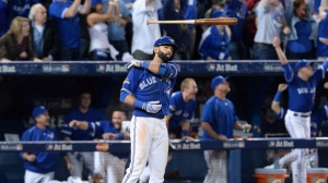 Toronto Blue Jays Jose Bautista flips his bat after hitting a three-run homer during seventh inning game 5 American League Division Series baseball action in Toronto on Wednesday, Oct. 14, 2015. Jose Bautista's infamous bat flip is being commemorated on a baseball card. THE CANADIAN PRESS/Chris Young