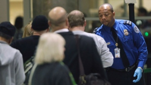 A TSA official checks passengers entering a security checkpoint at Hartsfield-Jackson Atlanta International Airport Thursday, Nov. 18, 2010 in Atlanta. (AP Photo/David Goldman)