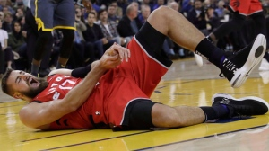 Toronto Raptors center Jonas Valanciunas reacts after injuring his hand during the first half of an NBA basketball game against the Golden State Warriors in Oakland, Calif., Wednesday, Dec. 12, 2018. (AP Photo/Jeff Chiu)