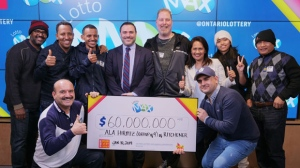 A group of coworkers poses with a giant cheque, after winning $60-million lottery jackpot, in Toronto in this Thursday, Jan. 10, 2019 handout photo. (THE CANADIAN PRESS/HO - OLG)