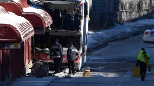 Transport Canada officials look at the scene where a double-decker city bus struck a transit shelter at the start of the afternoon rush hour on Friday, at Westboro Station in Ottawa, on Saturday, Jan. 12, 2019. THE CANADIAN PRESS/Justin Tang