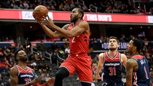 Toronto Raptors forward Kawhi Leonard (2) goes to the basket against Washington Wizards forward Jeff Green (32), guard Tomas Satoransky (31), of the Czech Republic, and forward Trevor Ariza (1) during the first half of an NBA basketball game, Sunday, Jan. 13, 2019, in Washington. (AP Photo/Nick Wass)