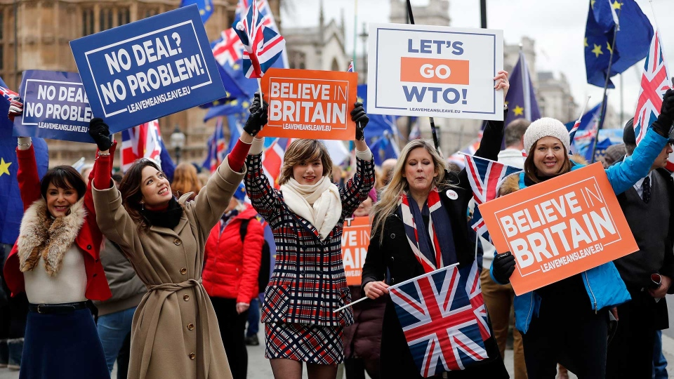 Leavers hold up signs next to pro-European demonstrators protesting opposite the Houses of Parliament in London, Tuesday, Jan. 15, 2019. (AP Photo/Frank Augstein)