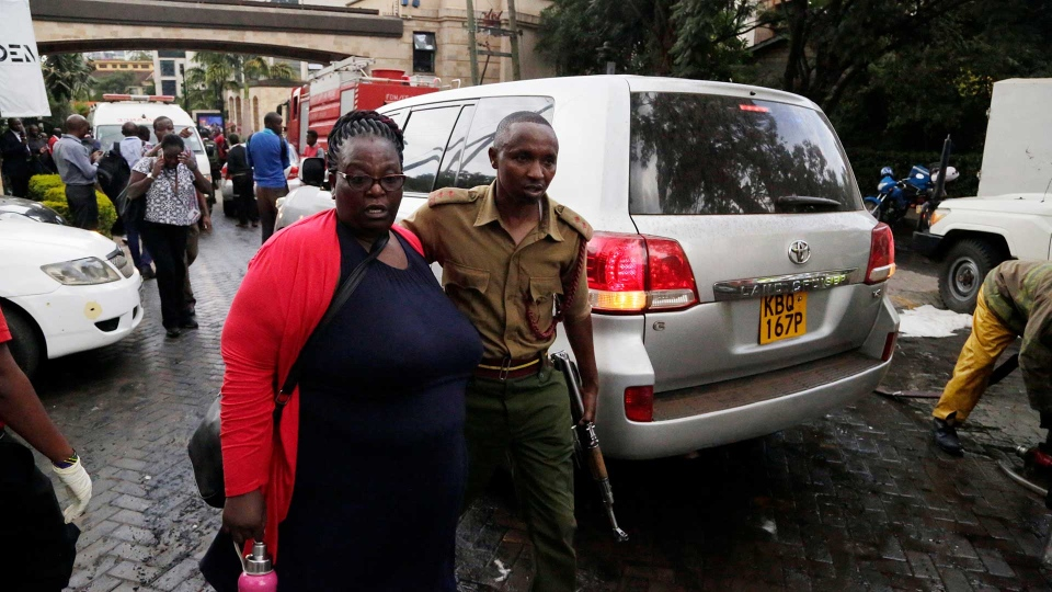 Security forces helps a woman at the scene of a blast in Nairobi, Kenya Tuesday, Jan. 15, 2019. An upscale hotel complex in Kenya's capital came under attack on Tuesday, with a blast and heavy gunfire. The al-Shabab extremist group based in neighboring Somalia claimed responsibility and said its members were still fighting inside. (AP Photo/Khalil Senosi)