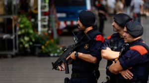 In this Friday, Aug. 17, 2018 file photo, Catalan police officers secure the area where a van driven by the attacker stopped in Barcelona, Spain. Authorities in the northeastern Spanish region of Catalonia said 17 people, including five alleged members of an extremist Islamic cell, were arrested Tuesday, Jan. 15, 2019 as part of an ongoing anti-terror operation. The Mossos d'Esquadra regional police said the arrests were conducted on terror-related links but also on evidence that the suspects allegedly committed theft, drug trafficking and other crimes. (AP Photo/Emilio Morenatti, File)