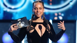 In this Jan. 28, 2018 file photo, Alicia Keys presents the award for record of the year at the 60th annual Grammy Awards at Madison Square Garden in New York. The Recording Academy announced Tuesday, Jan. 15, 2019, that Keys will host the Feb. 10 Grammys for the first time. The show will air live on CBS in Los Angles. (Photo by Matt Sayles/Invision/AP, File)