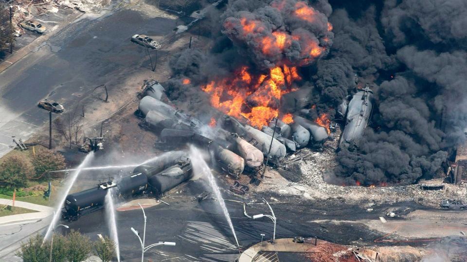 Smoke rises from railway cars that were carrying crude oil after derailing in downtown Lac-Megantic, Que., Saturday, July 6, 2013. THE CANADIAN PRESS/Paul Chiasson