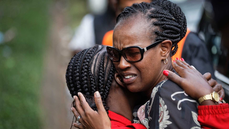 Unidentified women console each other at the scene of a violent attack early Wednesday, Jan. 16, 2019, in Nairobi, Kenya. Extremists stormed a luxury hotel in Kenya's capital on Tuesday, setting off thunderous explosions and gunning down people at cafe tables in an attack claimed by Africa's deadliest Islamic militant group. (AP Photo/Ben Curtis)