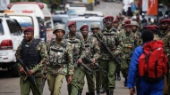 Kenyan security forces walk from the scene as continued blasts and gunfire could be heard early Wednesday, Jan. 16, 2019, in Nairobi, Kenya. Extremists stormed a luxury hotel in Kenya's capital on Tuesday, setting off thunderous explosions and gunning down people at cafe tables in an attack claimed by Africa's deadliest Islamic militant group. (AP Photo/Ben Curtis)