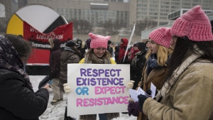 Simone Robbins holds a sign during the start of the Toronto Women's March at Nathan Phillips Square on Saturday, January 19, 2019. THE CANADIAN PRESS/ Tijana Martin