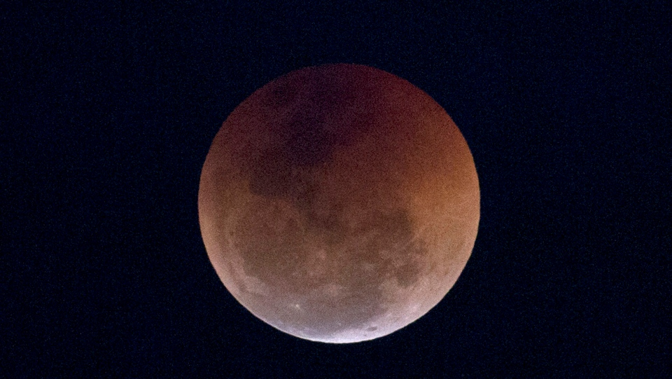 FILE - This Friday, July 27, 2018 file photo shows a blood moon lunar eclipse from the Arpoador beach in Rio de Janeiro, Brazil. Starting Sunday evening, Jan. 20, 2019, all of North and South America will be able to see the only total lunar eclipse of 2019 from start to finish this weekend. (AP Photo/Silvia Izquierdo)