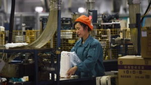 A woman packs paper tablewares at a factory in Hangzhou, China's Zhejiang province, Monday, Jan. 21, 2019. China's 2018 economic growth fell to a three-decade low of 6.6 percent amid a tariff battle with Washington. Growth in the final quarter of the year decelerated to 6.4 percent. (Chinatopix via AP)
