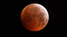 The full moon is seen during a lunar eclipse in Marseille, southern France, Monday Jan. 21 2019. It's also the year's first supermoon, when a full moon appears a little bigger and brighter thanks to its slightly closer position to Earth. (AP Photo/Claude Paris)