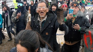 FILE - In this Feb. 22, 2017, file photo, a large crowd representing a majority of the remaining Dakota Access Pipeline protesters, including Nathan Phillips, center with glasses, march out of the Oceti Sakowin camp before the deadline set for evacuation of the camp near Cannon Ball, N.D. Phillips says he felt compelled to get between a group of black religious activists and largely white students with his ceremonial drum to defuse a potentially dangerous situation at a rally in Washington. (Mike McCleary/The Bismarck Tribune via AP, File)