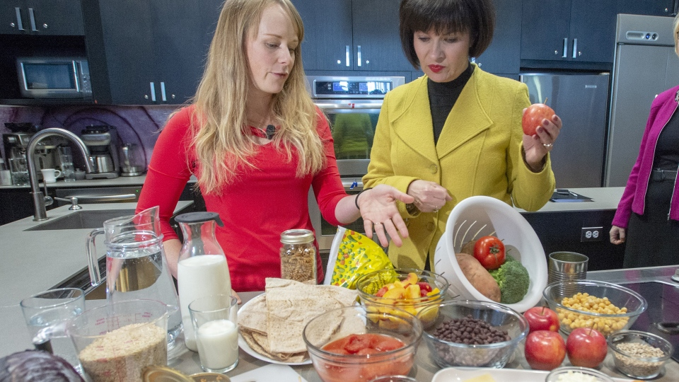 Health Minister Ginette Petitpas Taylor, right, and nutritionist Jessica Cole look over samples of some of the food groups at the unveiling of Canada's new Food Guide, Tuesday, January 22, 2019 in Montreal.THE CANADIAN PRESS/Ryan Remiorz