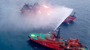 In this video grab provided by Russia Emergency Situations Ministry press service, a Russia Emergency Situations Ministry ship works to extinguish a fire on the two vessels, the Maestro and the Candiy, near the Kerch Strait linking the Black Sea and the Sea of Azov, Crimea, Tuesday, Jan. 22, 2019. Two Tanzanian-flagged tankers caught fire Monday while liquefied petroleum gas was being pumped from one tanker to another. The blaze spread quickly, prompting the crews to jump overboard. The ships were about 30 kilometers (15 nautical miles) off the Crimean coast when the fire started. (Russia Emergency Situations Ministry press service via AP)