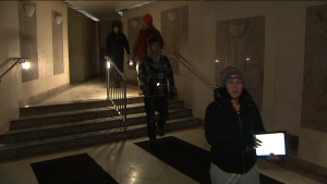 Residents are seen using flashlights as they navigate the hallways of a high-rise at 260 Wellesley Street East on Tuesday afternoon. Power and water has been shut off to the building due to a burst pipe in its electrical room.