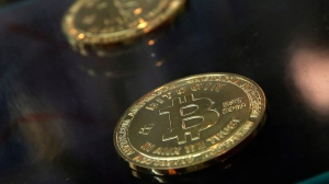 FILE- In this Dec. 8, 2017, file photo, coins are displayed next to a Bitcoin ATM in Hong Kong (AP Photo/Kin Cheung, File)