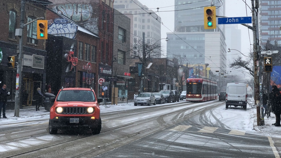 Vehicles move along Queen St. W., as snow falls on Friday, Jan. 25, 2019. (Sumran Bhan/CP24.com)