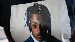 In this June 27, 2018, file photo a fan wears a cross around her neck dangling on a t-shirt in remembrance before she enters a memorial for the rapper, XXXTentacion in Sunrise, Fla. (AP Photo/Brynn Anderson, File)