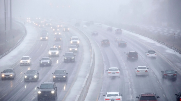 Cars drive along Toronto's Lakeshore Drive as visibility diminishes through falling hail, snow, and rain in Toronto, Ontario on Saturday, April 14, 2018. THE CANADIAN PRESS/Cole Burston