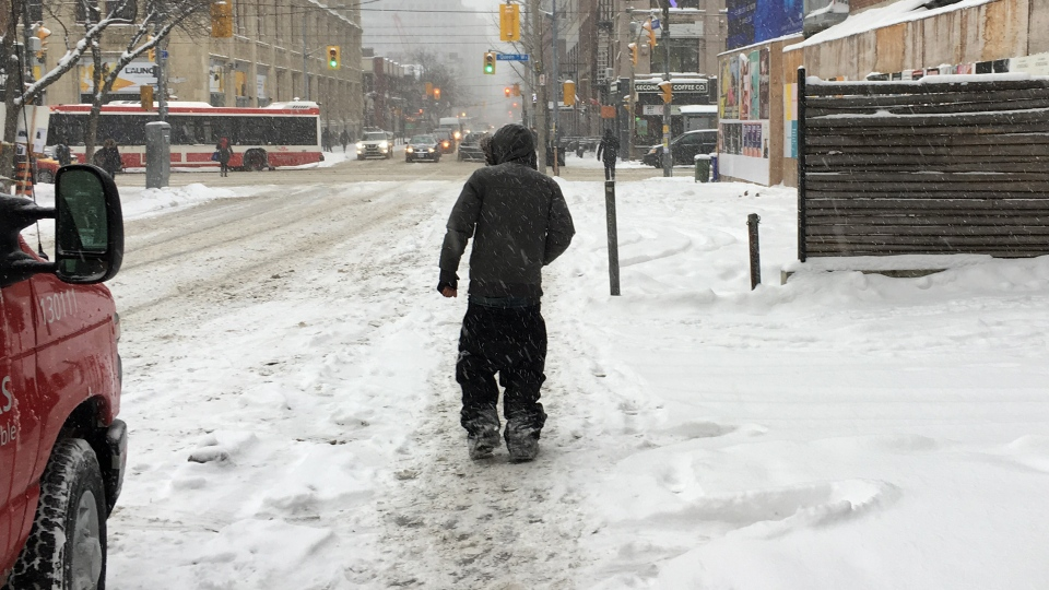 A man walks down a snow-covered sidewalk on John Street in downtown Toronto Monday January 28, 2019. (Joshua Freeman /CP24)