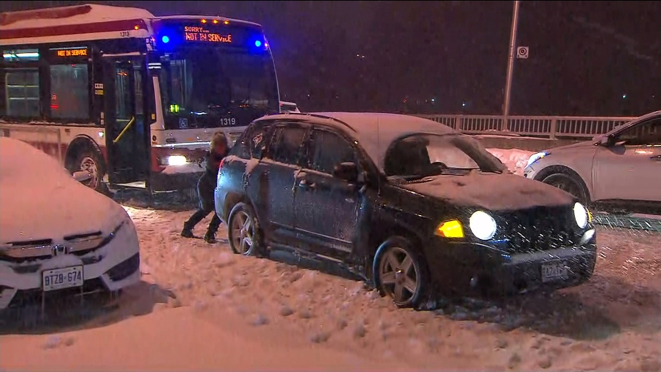 A woman struggles to free her car from a snow-covered road in Toronto Monday January 28, 2019.