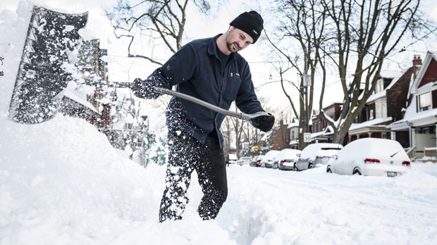 Jordan Poirier clears the sidewalk of snow in front of his home after a heavy winter storm, in Toronto on Tuesday, January 29, 2019. THE CANADIAN PRESS/Christopher Katsarov