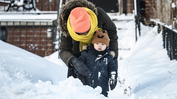 Nana Yanful brushes snow off of 21-month-old Addae Yanful Paterson before going to school after a heavy winter storm, in Toronto on Tuesday, January 29, 2019. THE CANADIAN PRESS/Christopher Katsarov