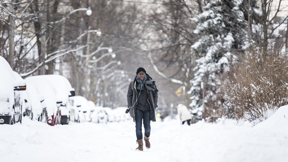 Bernard Otu walks down the middle of a road due to sidewalks being covered in snow after a heavy winter storm, in Toronto on Tuesday, January 29, 2019. THE CANADIAN PRESS/Christopher Katsarov