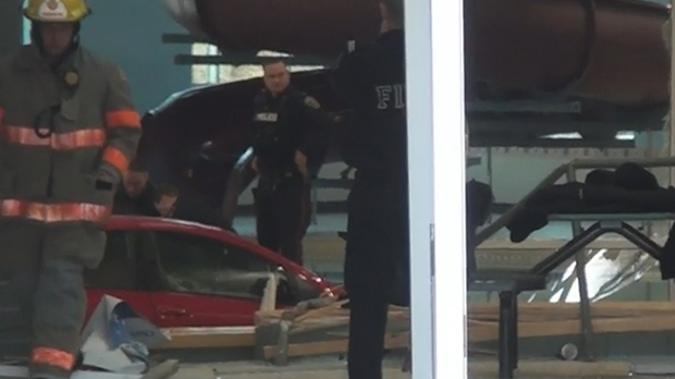 Police and fire crews stand next to a Toyota submerged in the pool at Courtice Community Centre on Jan. 25, 2019. (CTV News Toronto)