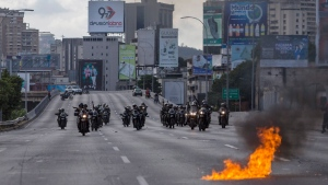 National Guard officers drive motorcycles as anti-government protesters block a highway with a small group of demonstrators who were returning from a peaceful demonstration called by self-declared interim president Juan Guaido to demand the resignation of President Nicolas Maduro, in Caracas, Venezuela, Saturday, Feb. 2, 2019. (AP Photo/Rodrigo Abd)