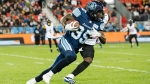 Toronto Argonauts running back Brandon Burks (35) is defended by Hamilton Tiger-Cats linebacker Larry Dean (11) during first half CFL football action in Toronto on Friday, Oct. 12, 2018. THE CANADIAN PRESS/Christopher Katsarov