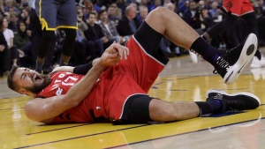 Toronto Raptors center Jonas Valanciunas reacts after injuring his hand during the first half of an NBA basketball game against the Golden State Warriors in Oakland, Calif., on December 12, 2018. The Toronto Raptors say the injury to centre Jonas Valanciunas's left thumb continues to improve, though the team did not provide a date for his return. THE CANADIAN PRESS/AP, Jeff Chiu