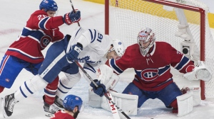 Toronto Maple Leafs' John Tavares (91) is pushed into Montreal Canadiens goaltender Carey Price by Canadiens' Jeff Petry (26) during first period NHL hockey action in Montreal, Saturday, Feb. 9, 2019. THE CANADIAN PRESS/Graham Hughes