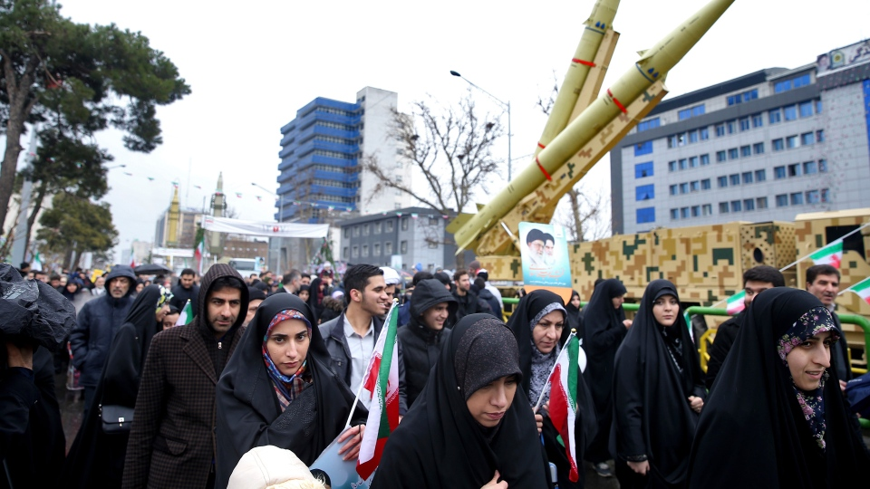Iranians walk past a missile during a rally marking the 40th anniversary of the 1979 Islamic Revolution, in Tehran, Iran, Monday, Feb. 11, 2019. Hundreds of thousands of Iranians poured out onto the streets of Tehran and other cities and towns across the country, marking the date 40 years ago that is considered victory day in the country's 1979 Islamic Revolution. (AP Photo/Ebrahim Noroozi)