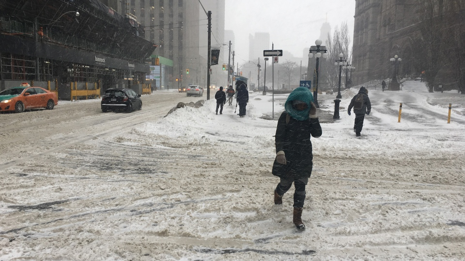 Pedestrians navigate a snowy sidewalk in downtown Toronto during a winter storm Tuesday February 12, 2019. (Joshua Freeman /CP24)