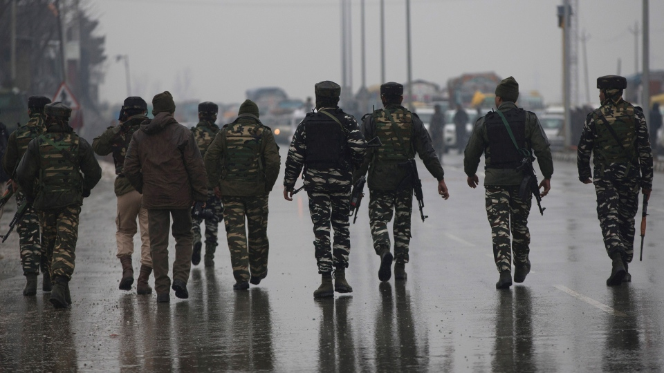 Indian paramilitary soldiers patrol near the site of an explosion in Pampore, Indian-controlled Kashmir, Thursday, Feb. 14, 2019. (AP Photo/Dar Yasin)