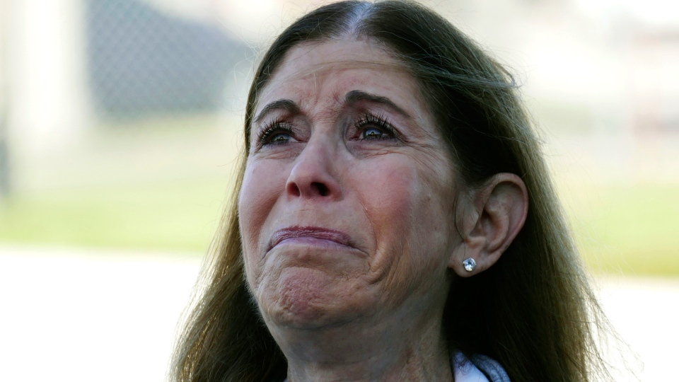 Linda Beigel Schulman, mother of Scott Beigel, a geography teacher and cross country coach who was killed in last year's mass shooting at Marjory Stoneman Douglas High School, becomes emotional while speaking to the media about her son, Thursday, Feb. 14, 2019, in Parkland, Fla. (Emily Michot/Miami Herald via AP)