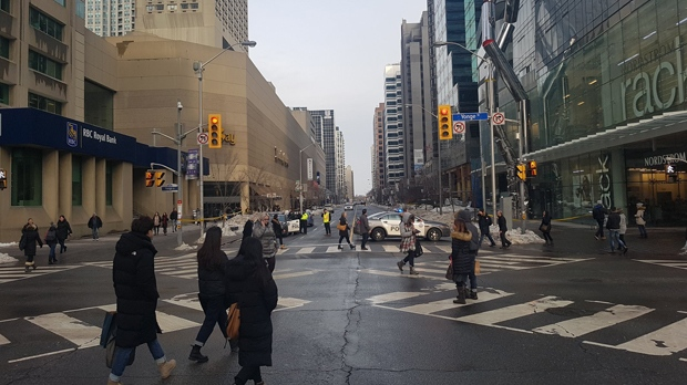 Police are seen blocking Bloor Street East at Yonge after glass fell from surrounding buildings onto the street and sidewalk on Feb. 14, 2019. (Twitter/@infinitism)