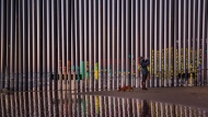 In this Jan. 3, 2019, file photo, a woman takes a snapshot by the border fence between San Diego, Calif., and Tijuana, as seen from Mexico. The immigration spending Congressional leaders on Thursday, Feb. 14, released details of a compromise on border and immigration enforcement that gives President Donald Trump just a sliver of the money he wanted for his border wall with Mexico. (AP Photo/Daniel Ochoa de Olza, File)