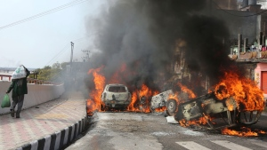 A man walks past vehicles set on fire by a mob during a protest against Thursday's attack on a paramilitary convoy, in Jammu, India, Friday, Feb.15, 2019. The death toll from a car bombing on the paramilitary convoy in Indian-controlled Kashmir has climbed at least 40, becoming the single deadliest attack in the divided region's volatile history, security officials said Friday. (AP Photo/Channi Anand)