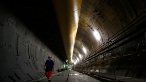 An engineer walks inside a Turin-Lyon high-speed rail tunnel (TAV) in Saint Martin La Porte, France, Tuesday, Feb. 12, 2019. The project is part of an European wide network to improve high-speed rail connections. On the Italian side, the construction site long targeted by sabotaging protesters is guarded by four law enforcement agencies and has been reduced to maintenance work only. The survival of Italy's increasingly uneasy populist government could very well depend on whether Italy restarts construction on the TAV link, which it halted in June. (AP Photo/Antonio Calanni)