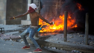 A protester throws a rock at national police during a demonstration demanding the resignation of Haitian President Jovenel Moise near the presidential palace in Port-au-Prince, Haiti, Wednesday, Feb. 13, 2019. Protesters are angry about skyrocketing inflation and the government's failure to prosecute embezzlement from a multi-billion Venezuelan program that sent discounted oil to Haiti. (AP Photo/Dieu Nalio Chery)