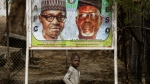 A young boy scavenges for re-sellable items from garbage on the streets, as he walks past a sign showing incumbent President Muhammadu Buhari, left, and local party official Mustapha Dankadai, right, in Kano, northern Nigeria Friday, Feb. 15, 2019. Nigeria is due to hold general elections on Saturday, pitting incumbent President Muhammadu Buhari against leading opposition presidential candidate Atiku Abubakar. (AP Photo/Ben Curtis)
