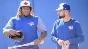 Toronto Blue Jays infielder Vladimir Guerrero Jr., left, arrives during baseball spring training in Dunedin, Fla., on Saturday, February 16, 2019. THE CANADIAN PRESS/Nathan Denette
