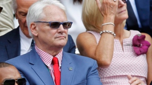 Canada's High Commissioner to London Gordon Campbell, center, sits in the Royal Box on centre court prior to the women's singles final between Eugenie Bouchard of Canada and Petra Kvitova of the Czech Republic at the All England Lawn Tennis Championships in Wimbledon, London, Saturday July 5, 2014. A global communications marketing firm says it is suspending its contract with former British Columbia premier Gordon Campbell in light of an allegation in a British newspaper that he groped a woman in the United Kingdom. THE CANADIAN PRESS/AP-Sang Tan