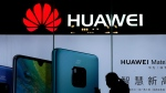 In this Dec. 11, 2018, file photo, a woman browses her smartphone as she walks by a Huawei store at a shopping mall in Beijing. (AP Photo/Andy Wong)