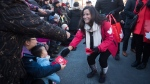 Then Veterans Affairs Minister Jody Wilson-Raybould, right, hands out lucky red envelopes while participating in the Chinese New Year Parade in Vancouver on February 10, 2019. THE CANADIAN PRESS/Darryl Dyck