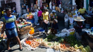 Residents shop at an open-air market in Port-au-Prince, Haiti, Monday, Feb. 18, 2019. Businesses and government offices slowly reopened across Haiti on Monday after more than a week of violent demonstrations over prices that have doubled for food, gas and other basic goods in recent weeks and allegations of government corruption. (AP Photo/Dieu Nalio Chery)